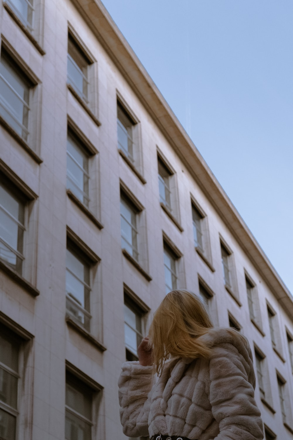 woman in white shirt standing near white concrete building during daytime