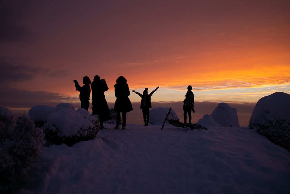 silhouette of people on snow covered ground during sunset