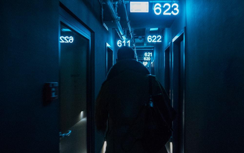 man in black hoodie standing in front of blue door