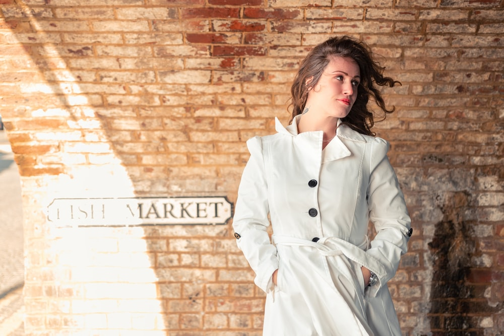 woman in white coat standing beside brick wall
