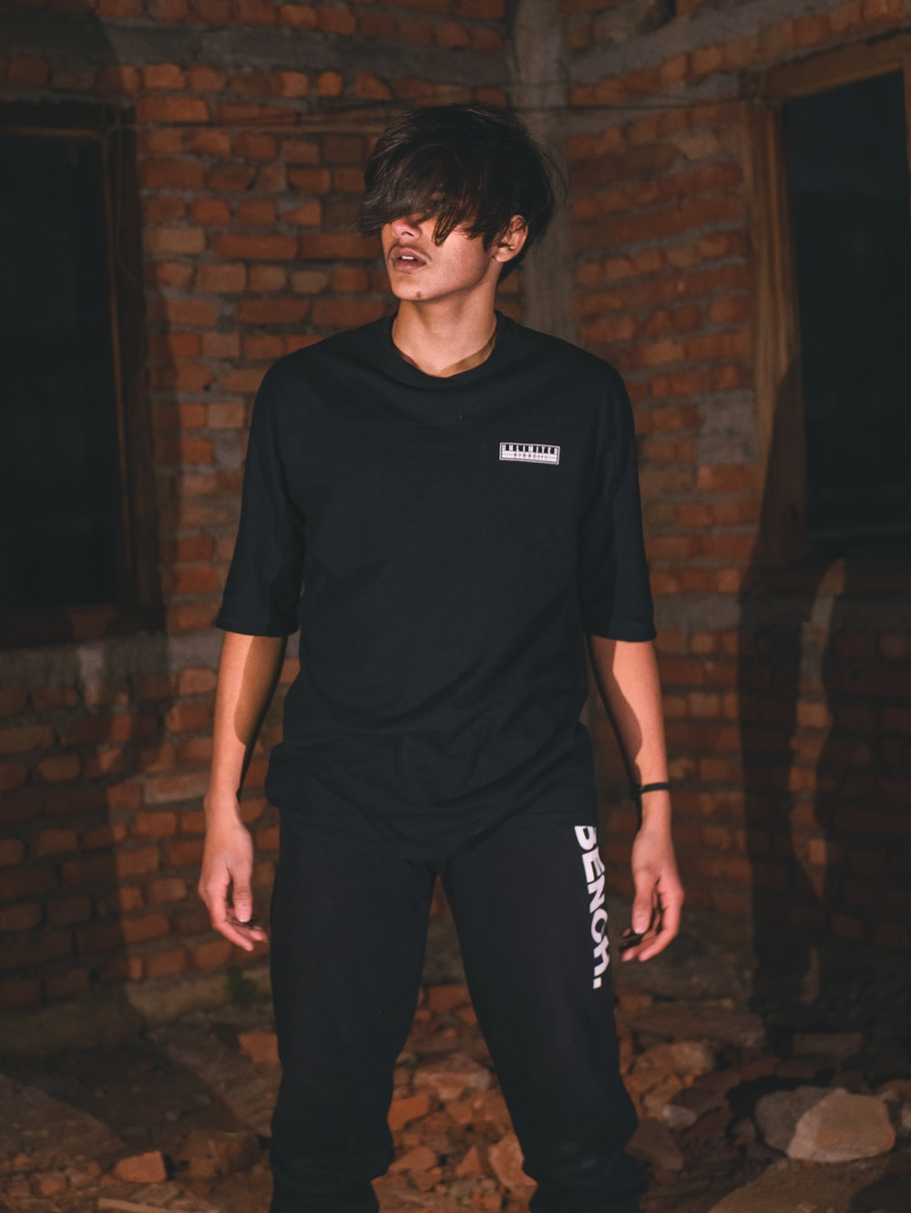 man in black crew neck t-shirt and black pants standing near brown brick wall