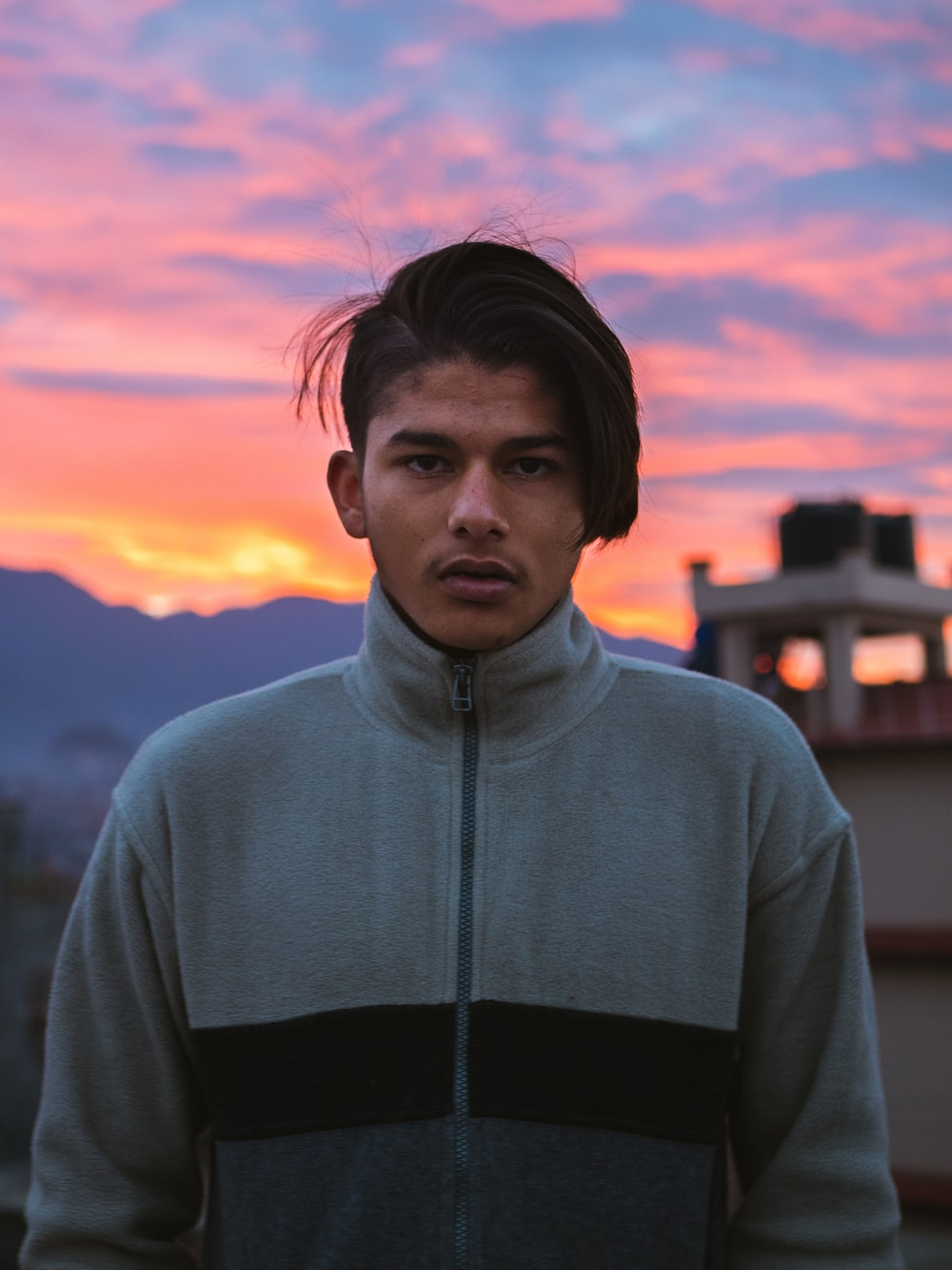 man in gray hoodie standing near building during sunset