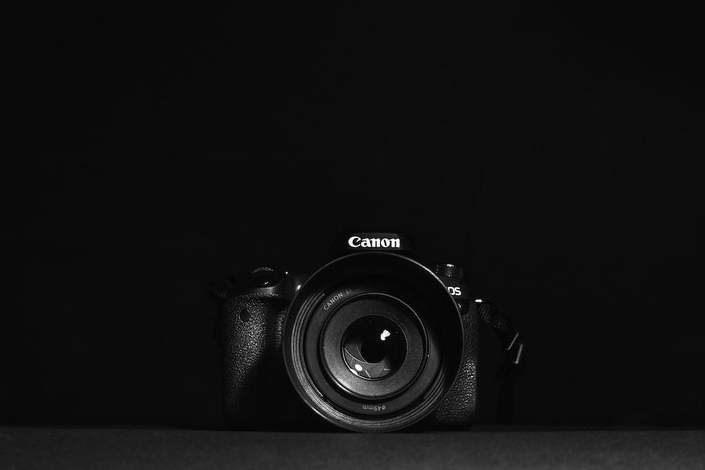 black nikon dslr camera on black textile