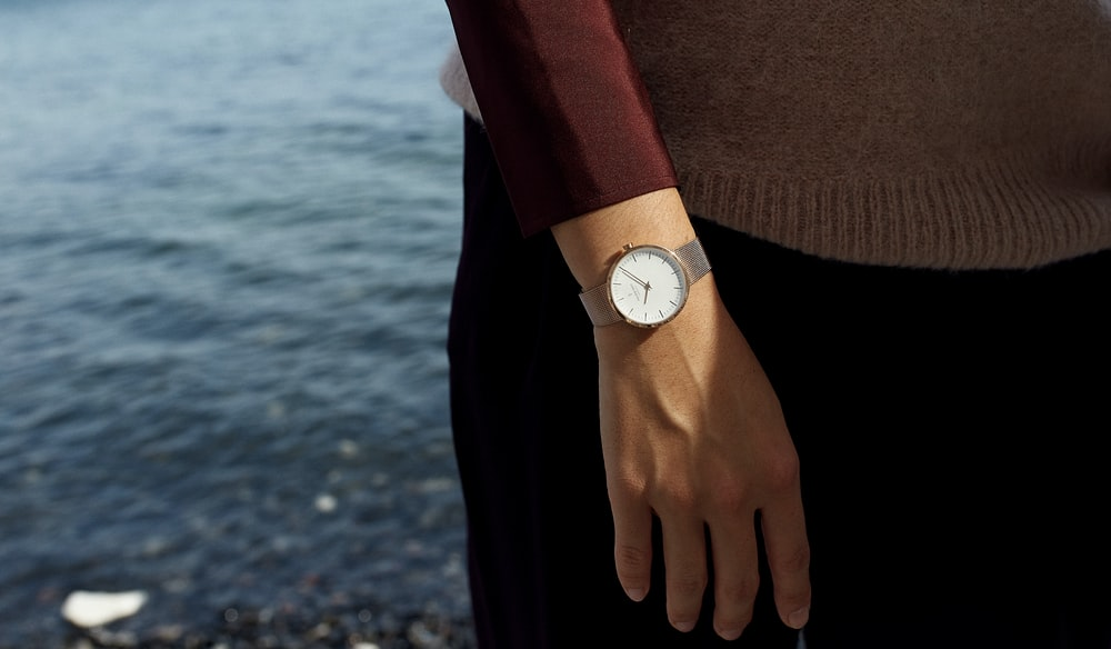 person in brown sweater and black pants wearing white analog watch