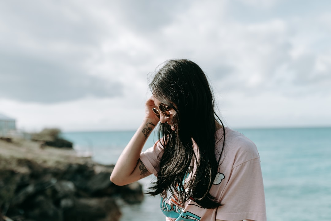 Woman In Brown Shirt Standing Near Body of Water During Daytime - unsplash