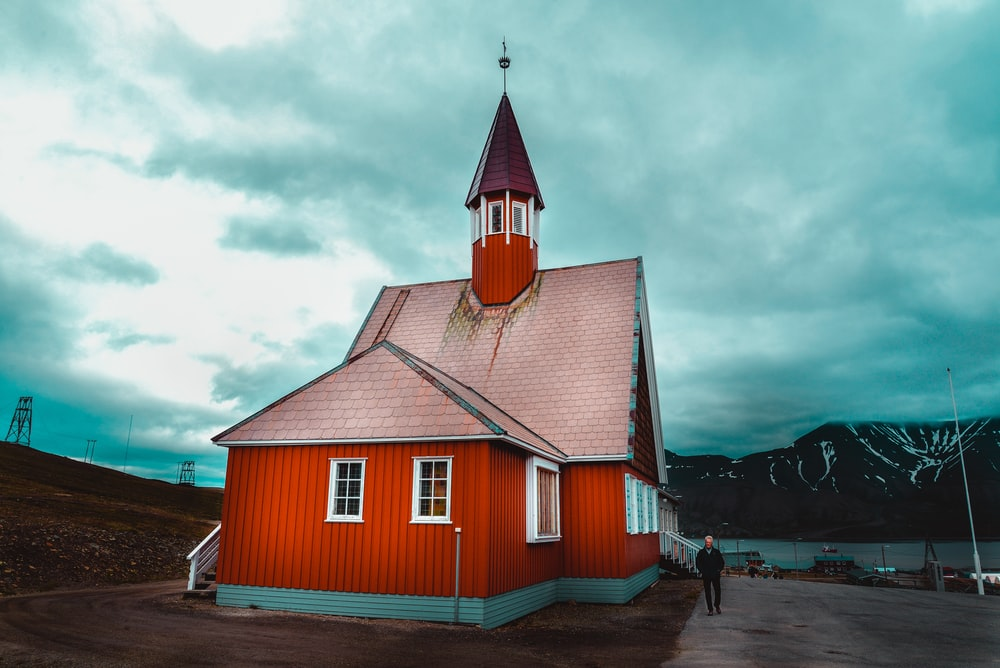red and brown wooden house under cloudy sky during daytime