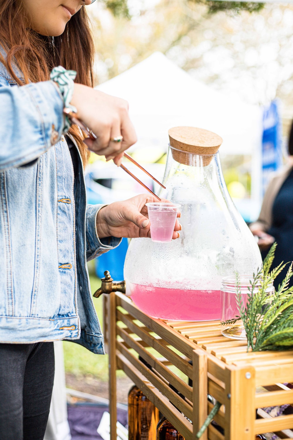 person in blue denim jacket holding clear glass pitcher with red liquid