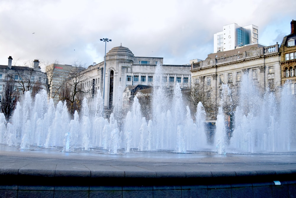 water fountain in front of brown concrete building during daytime