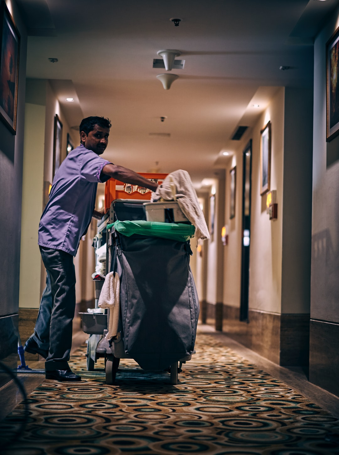 Room cleaning person in a hotel hallway with his equipments