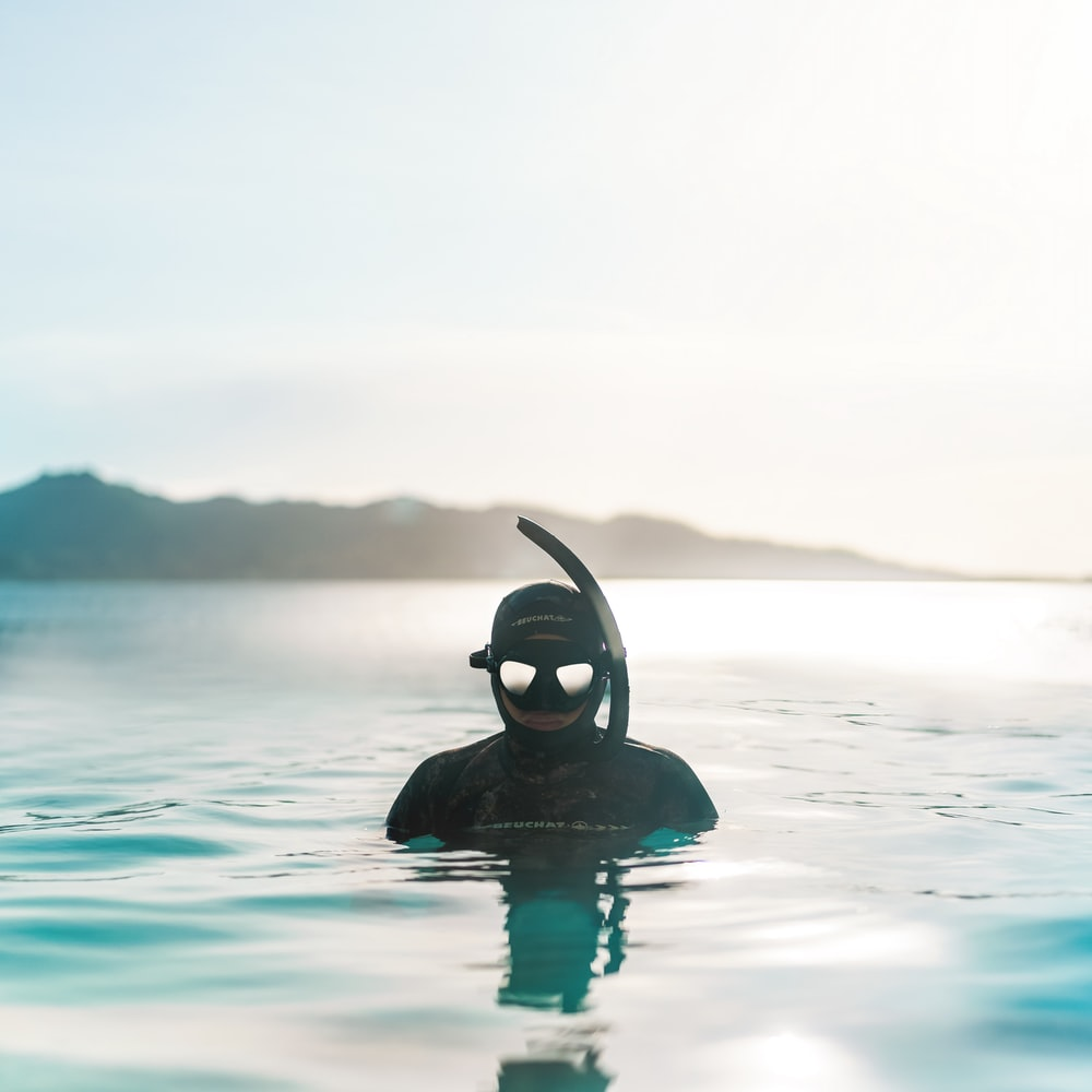 person in black swimming goggles in water