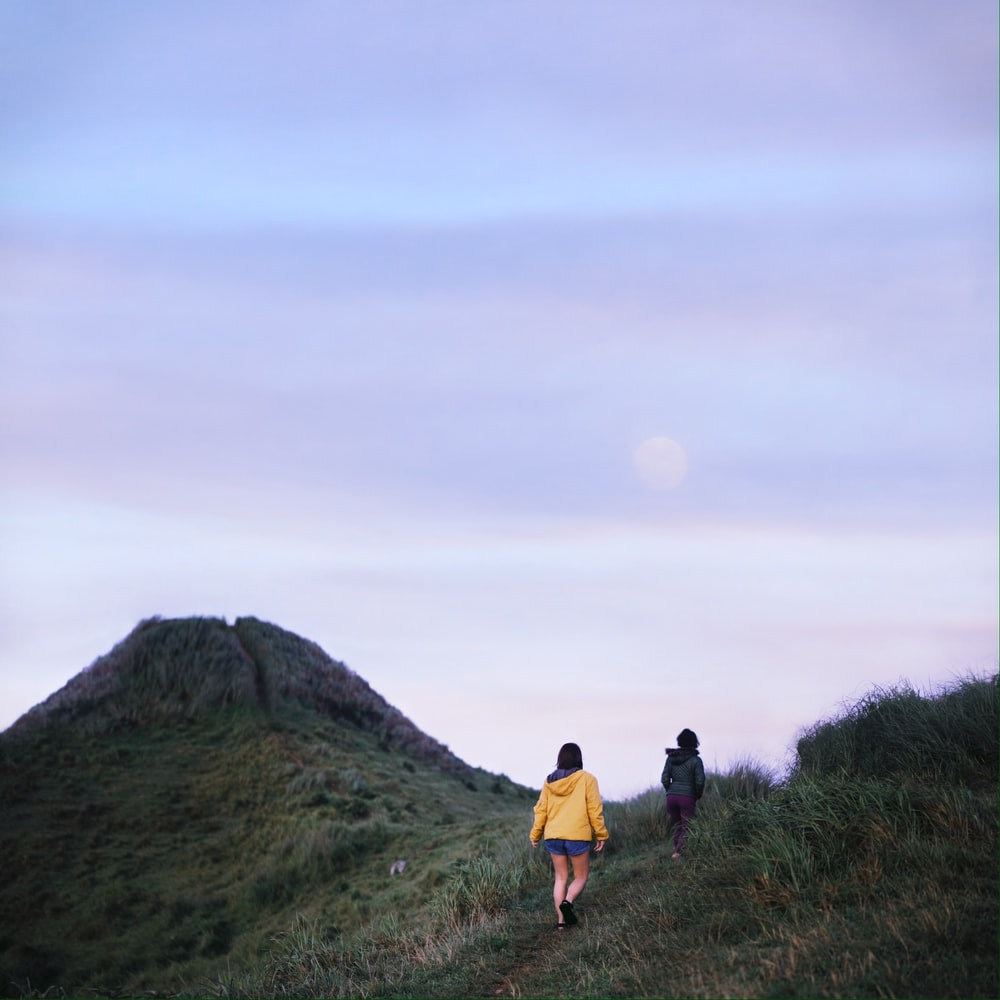 2 women walking on green grass field during daytime