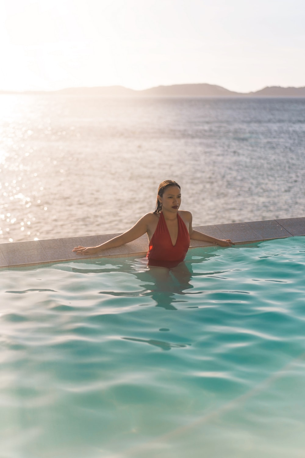 woman in red swimsuit in swimming pool during daytime