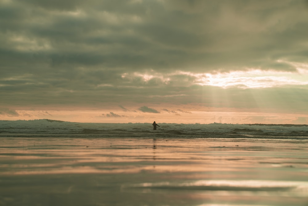 silhouette of person standing on sea shore during sunset