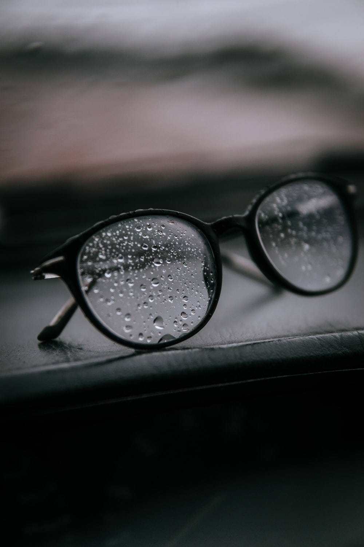 black framed eyeglasses on black surface
