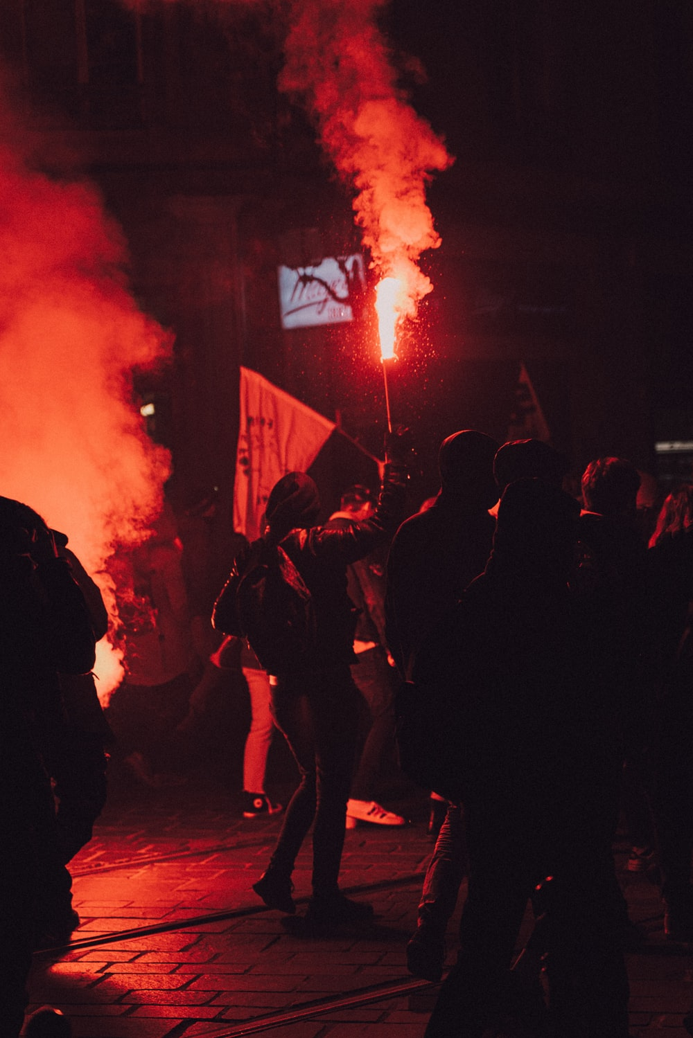 people standing on the street with red smoke