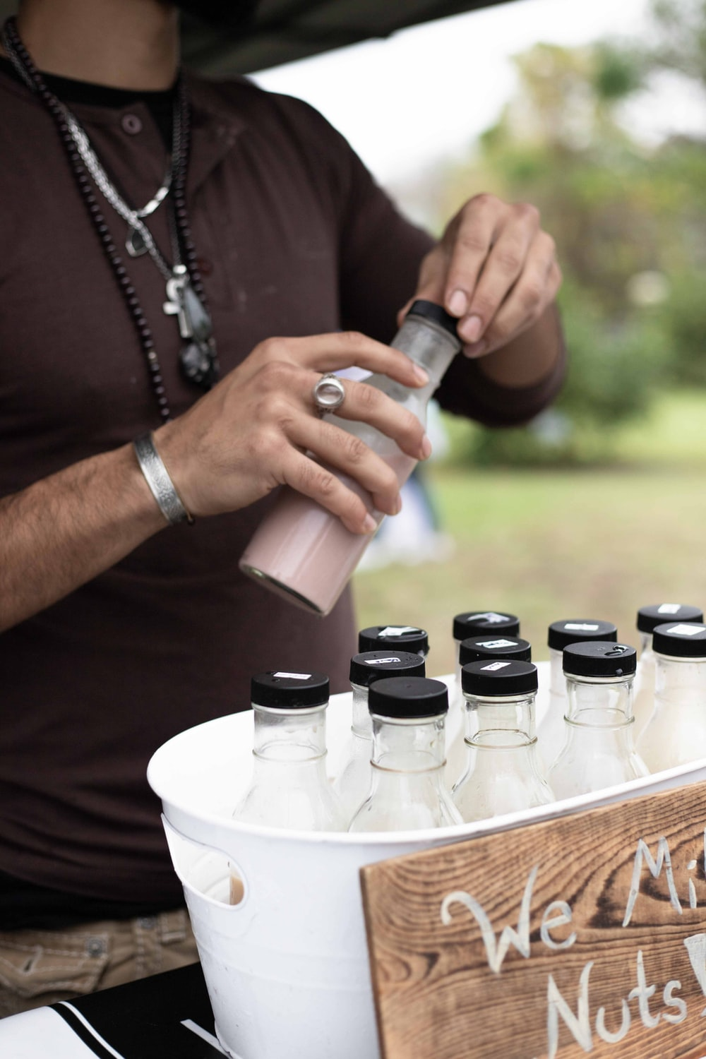 person holding black and white plastic bottles
