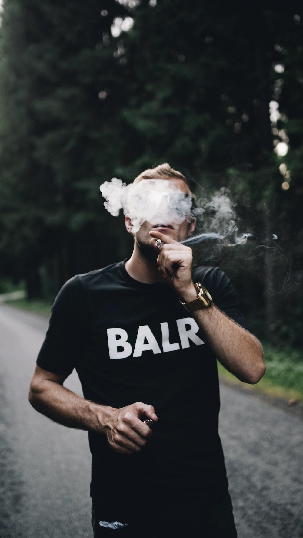 man in black crew neck t-shirt smoking cigarette