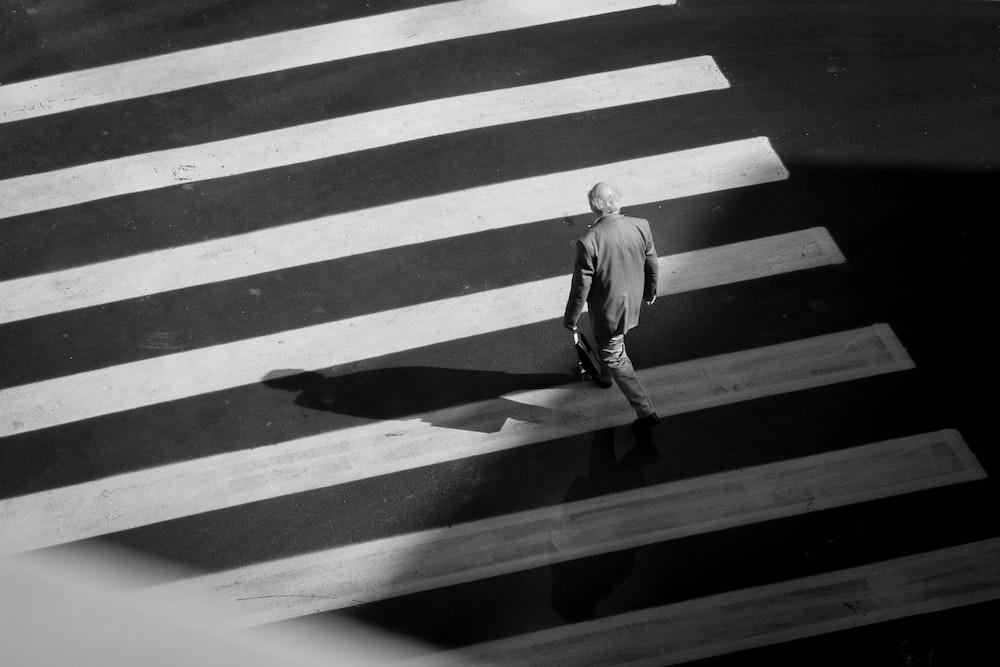man in white long sleeve shirt walking on pedestrian lane