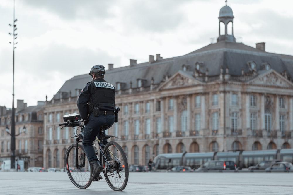 man in black jacket riding bicycle during daytime