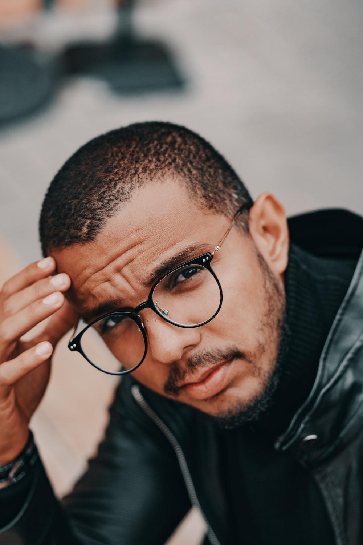 man in black framed eyeglasses and black jacket