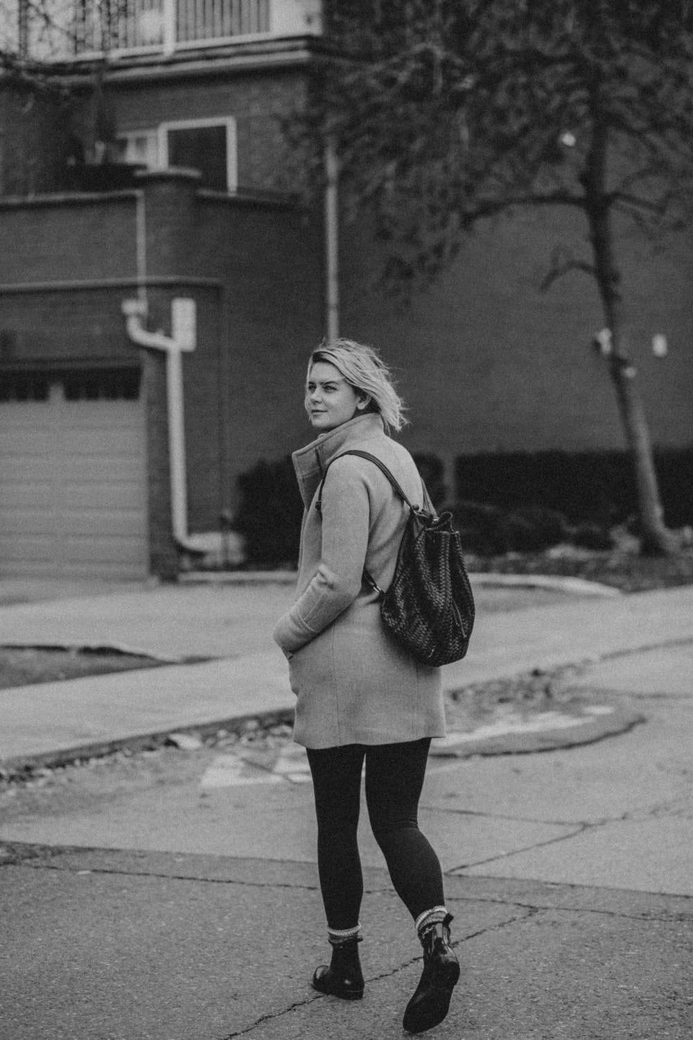 woman in jacket and pants standing on road
