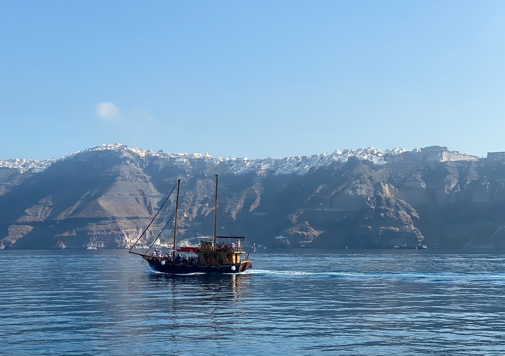 brown boat on sea near snow covered mountain during daytime