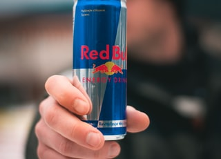 person holding red bull energy drink can