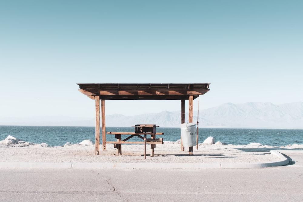 brown wooden beach dock on white sand beach during daytime