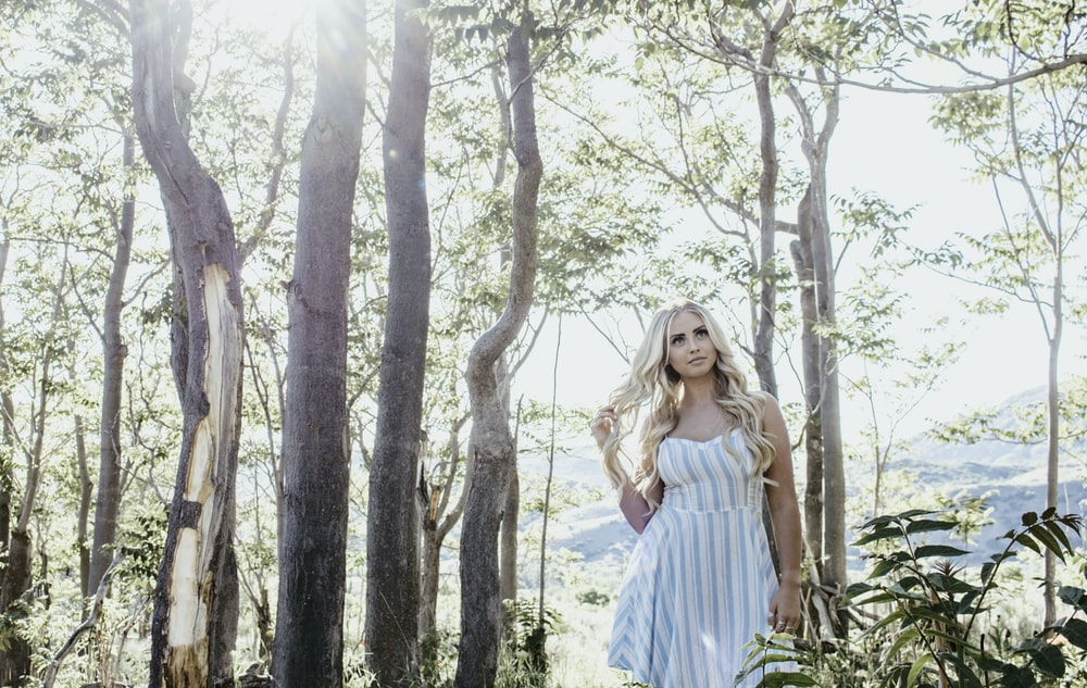 woman in white and blue striped dress standing under trees during daytime