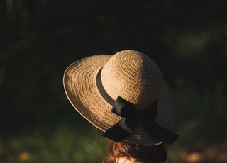 woman in black tank top wearing brown sun hat