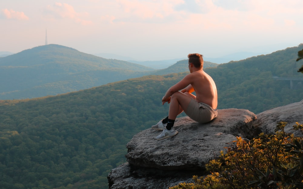 man in black shorts sitting on rock formation during daytime