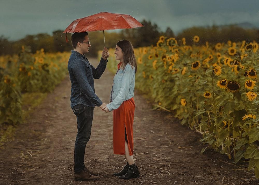 man and woman holding umbrella walking on pathway during daytime