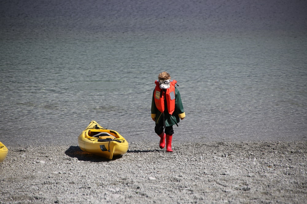 2 women in black and red suit carrying yellow and black inflatable ring on beach during