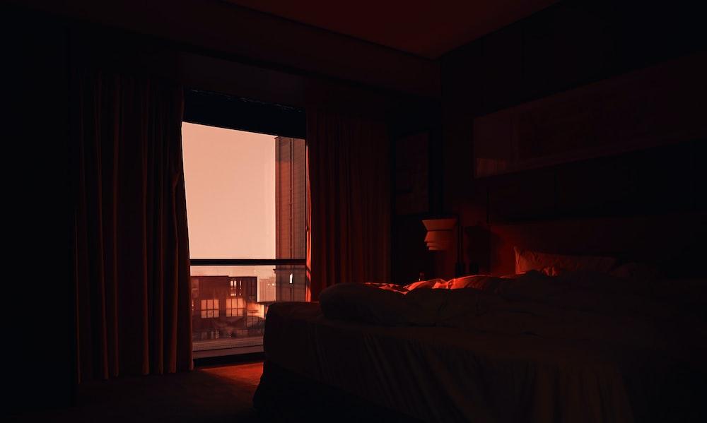 white bed linen near window