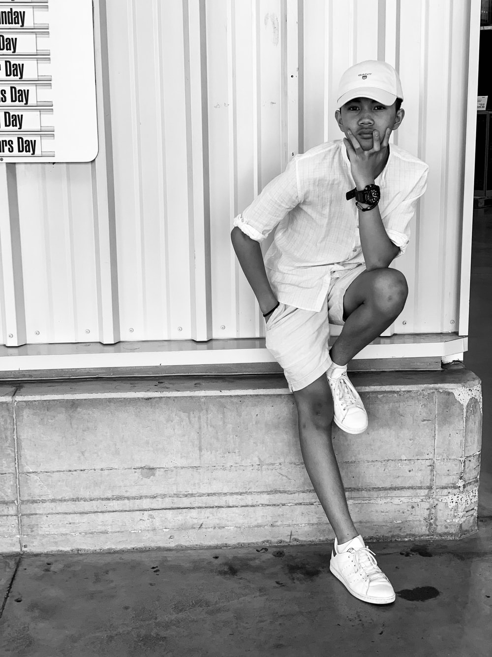 man in white t-shirt and white shorts sitting on white wooden wall