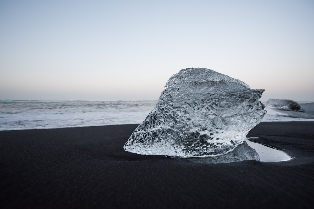 gray rock formation on black sand during daytime