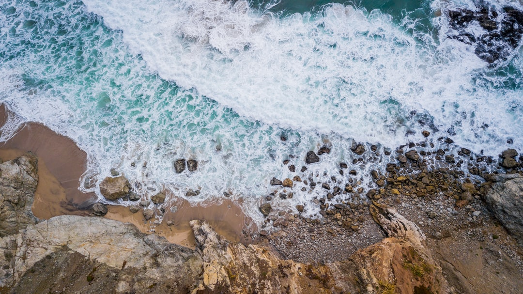 Brown Rocky Shore With Ocean Waves During Daytime - unsplash