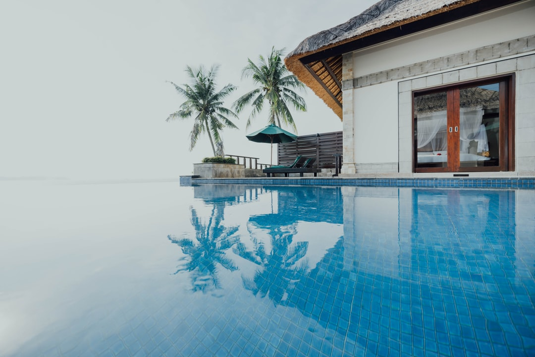 White and Brown House Near Swimming Pool During Daytime - unsplash