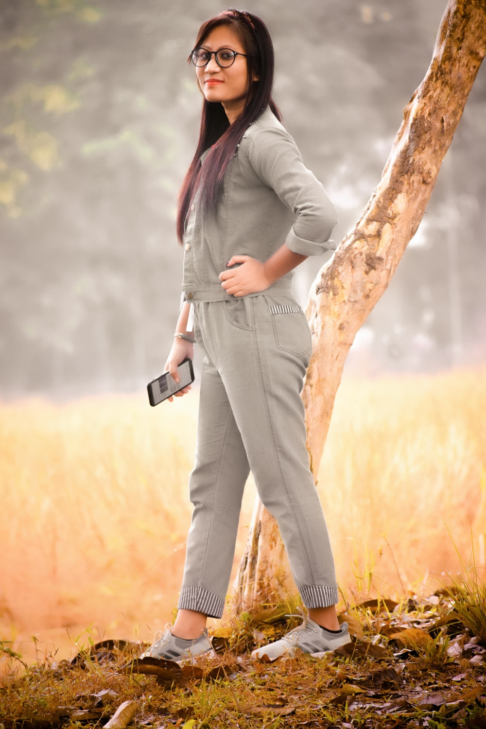 woman in gray jacket and brown pants standing on brown tree trunk during daytime