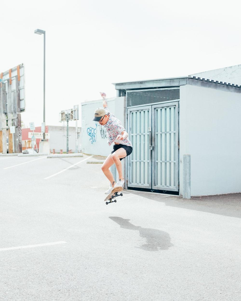 woman in white t-shirt and red shorts running on road during daytime