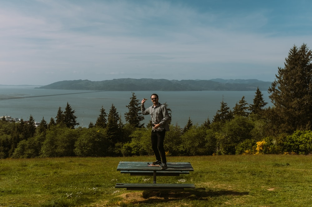 man in black jacket and blue denim jeans standing on blue wooden bench near green trees