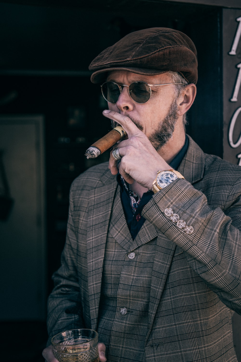 man in brown and black plaid coat smoking cigarette