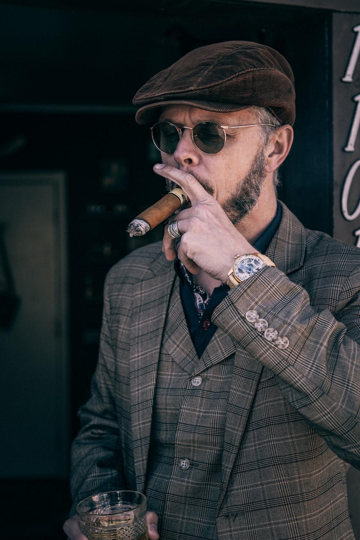 man in brown and black plaid coat smoking cigarette