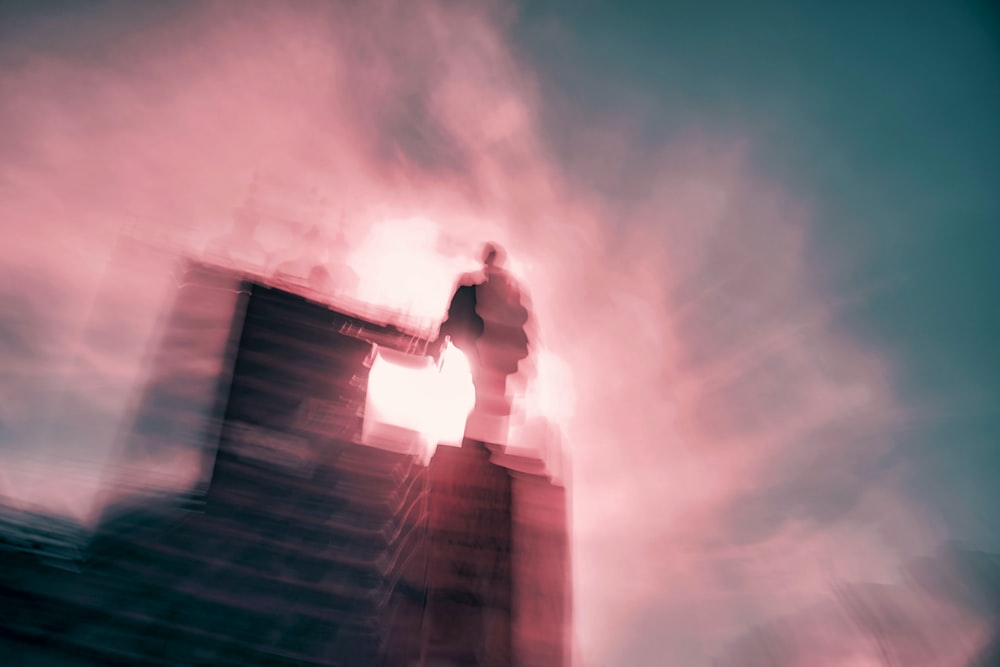 man in white shirt and black pants standing on top of building