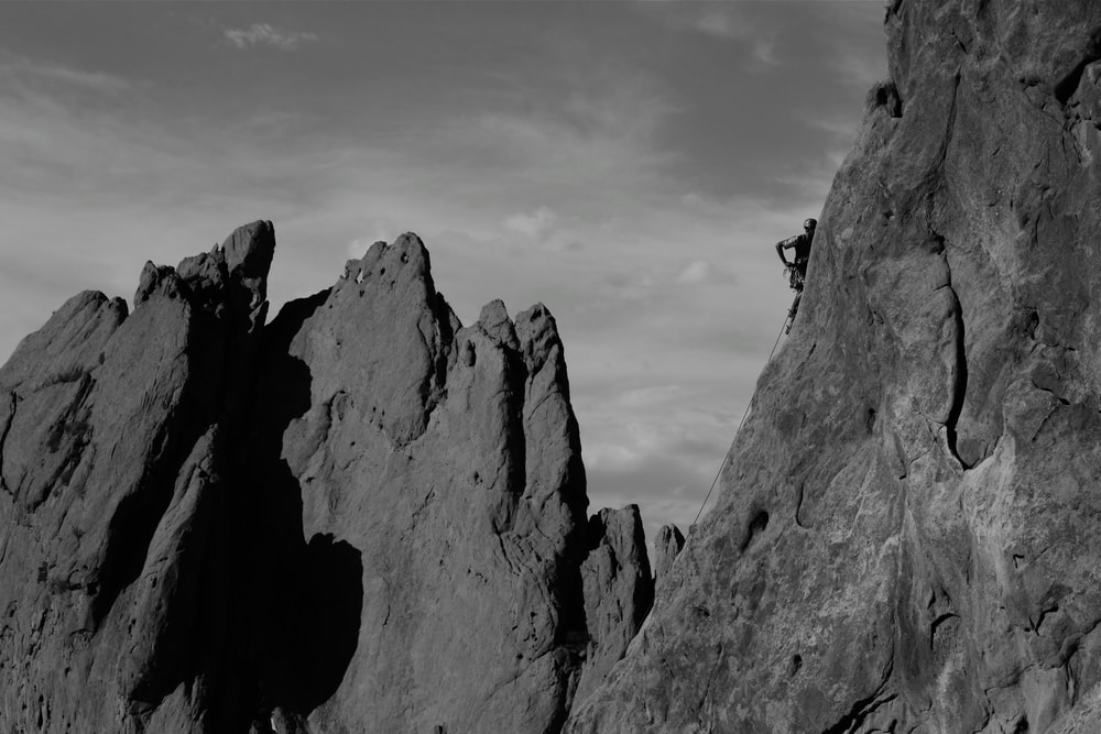 grayscale photo of person climbing on rock formation