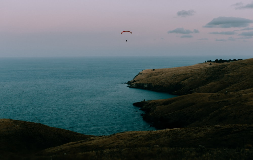 person in parachute over the sea during daytime