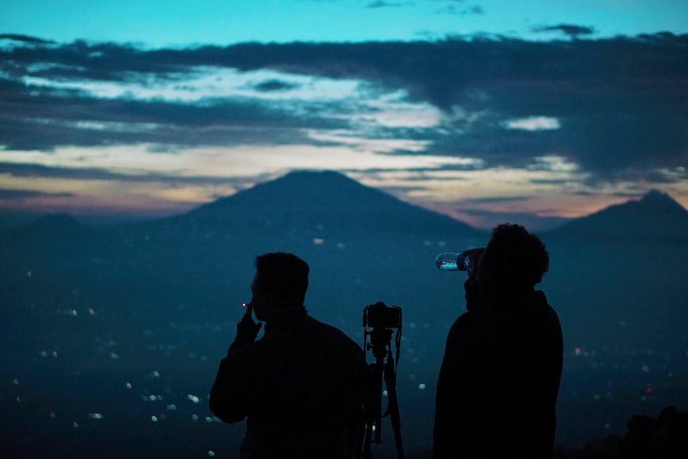 silhouette of 2 men standing near mountain during sunset