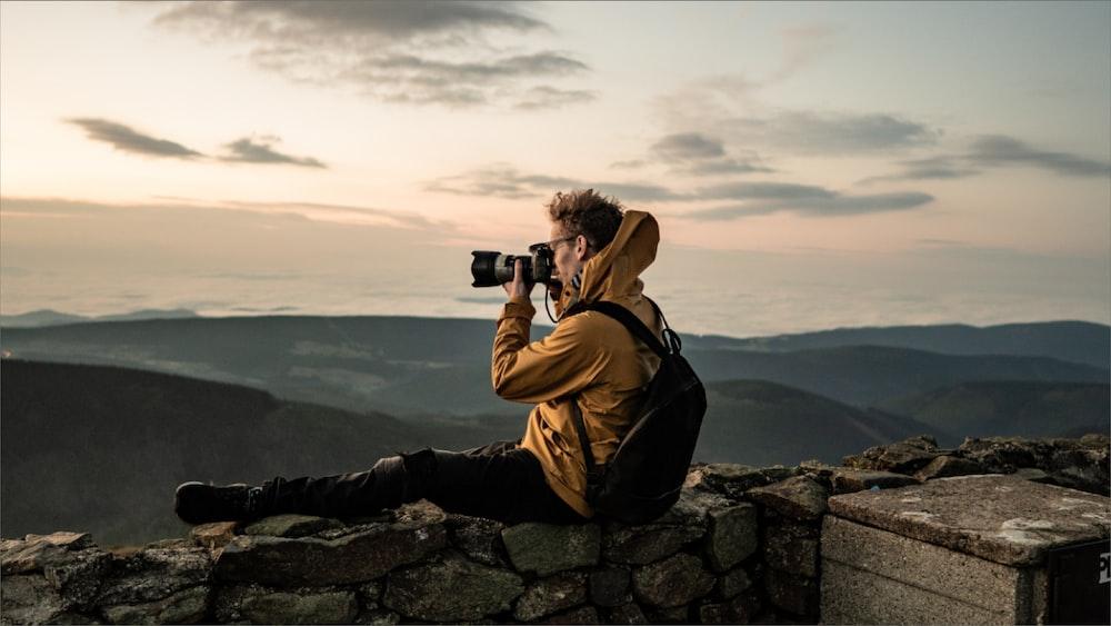 man in brown jacket taking photo of mountain during daytime