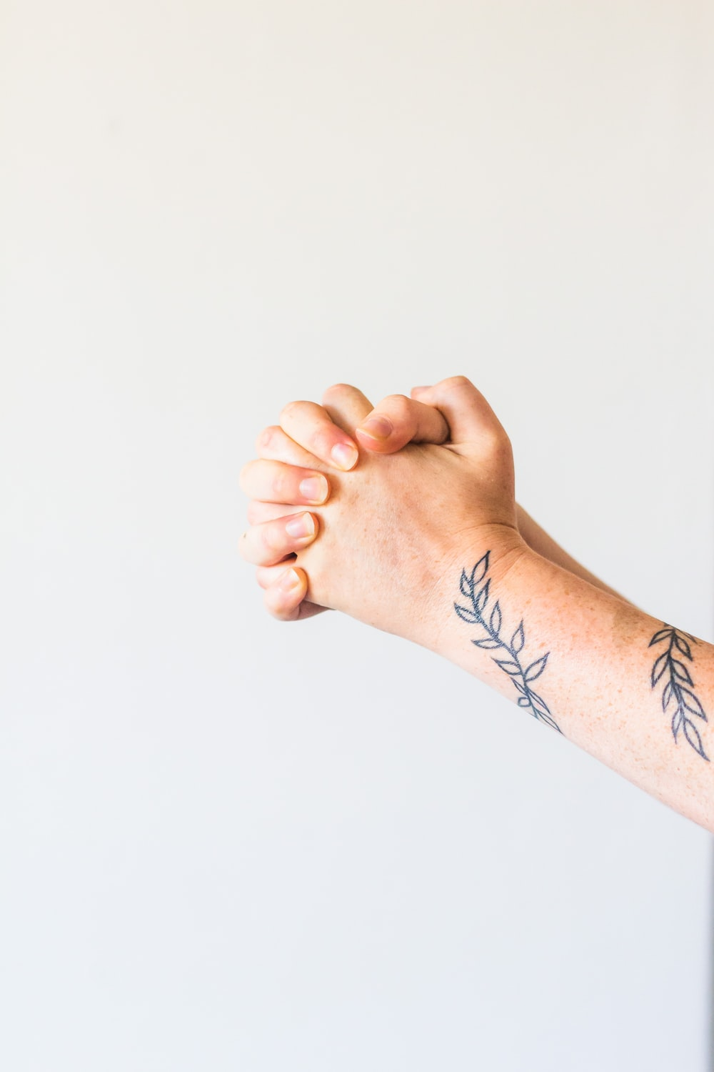 person with black and red tattoo on right hand