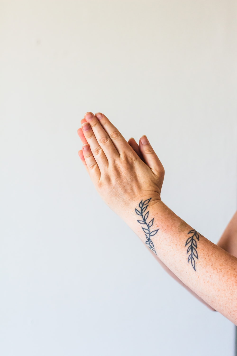 person with black tattoo on left hand
